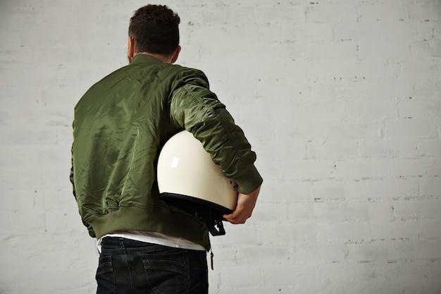 ジーンズの男の背中の肖像画、白で隔離の彼の腕の下に輝く白いオートバイのヘルメットとカーキ色のショートジャケット 無料写真