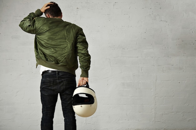 Back portrait of a young motorcyclist in jeans, military bomber jacket and holding his white helmet touching his hair isolated on white Free Photo