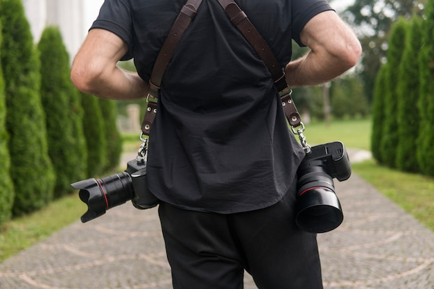 Back of professional photographer in black shirt and with a two cameras an a shoulder straps against the green garden. Premium Photo