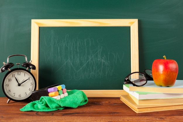 Back to school - apple and books with pencils and blackboard Premium Photo