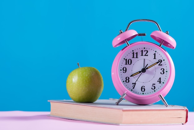 Back to school background with books,apple and alarm clock Free Photo