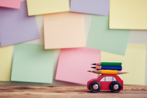 Back to school background with miniature red car carrying a colorful pencils over colorful stikers on wall Premium Photo