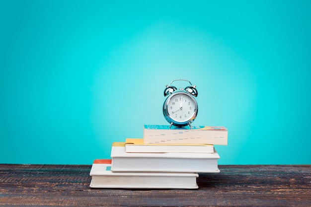 Back to school concept. books, colored pencils and clock Free Photo
