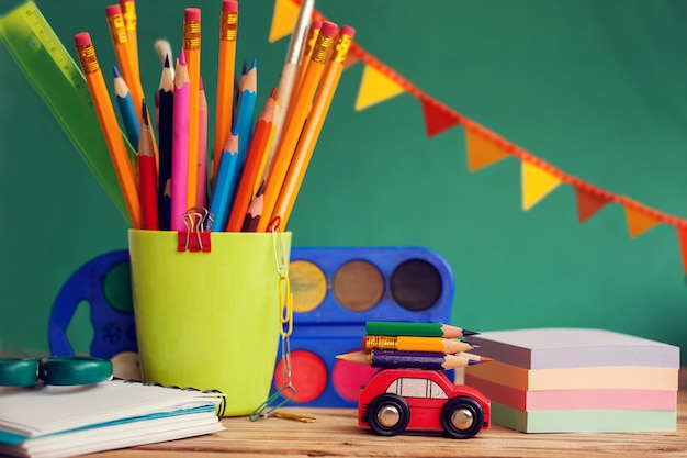 Back to school concept. group of school supplies: paint, pencils, paper, notepad on wooden table Premium Photo