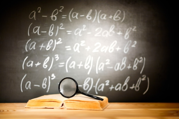 Back to school concept. old schoolbooks and magnifier lying on a wooden school desk in front of a black chalkboard with mathematical formulas school. Premium Photo