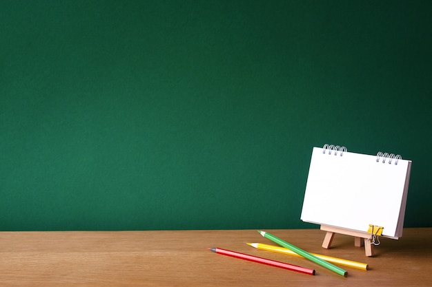 Back to school concept, open notebook on miniature easel and several colored pencils Premium Photo