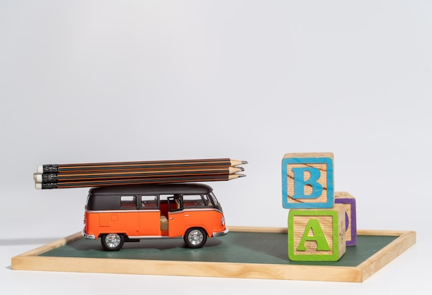 Back to school concept. school bus carry  pencils and letters block on blackboard Premium Photo