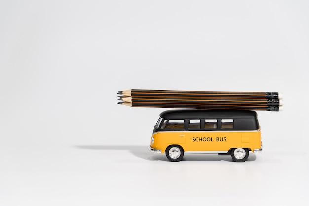 Back to school concept. school bus carry  pencils on white Premium Photo