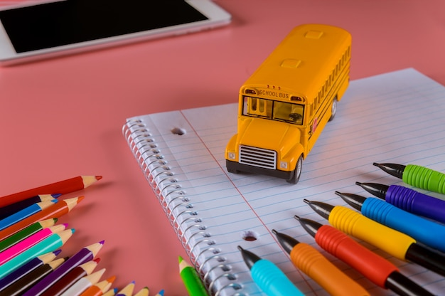 Back to school concept, school bus on notebook and pencils Premium Photo