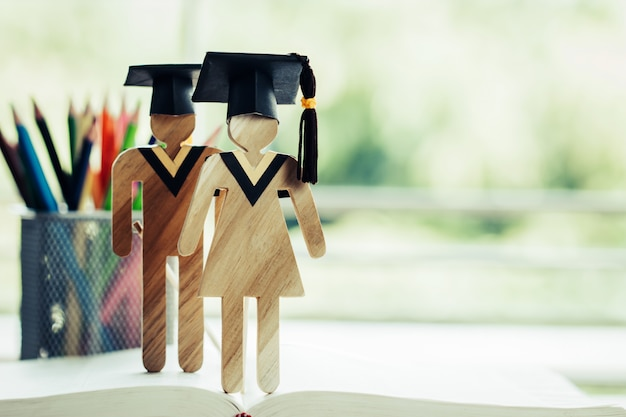 Back to school concept, two people sign wood with graduation celebrating cap on open textbook Premium Photo