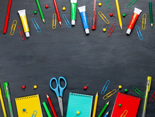 Back to school concept with colorful stationary over the blackboard Premium Photo
