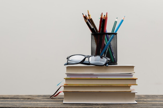 Back to school concept with glasses, books, pencils in holder on wooden and white wall side view. Free Photo