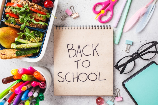 Back to school concept with lunch box with sandwich, fruit, snacks, notebook, pencils and school items Premium Photo