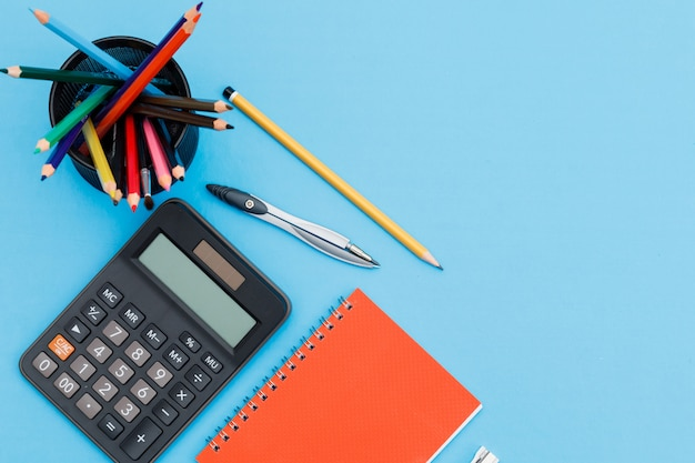 Back to school concept with notebook, pencils, calculator, compass on blue background flat lay. Free Photo