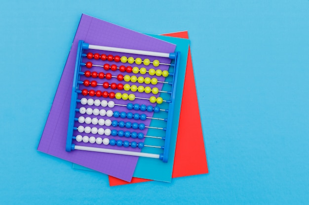 Back to school concept with notebooks, abacus on blue background flat lay. Free Photo