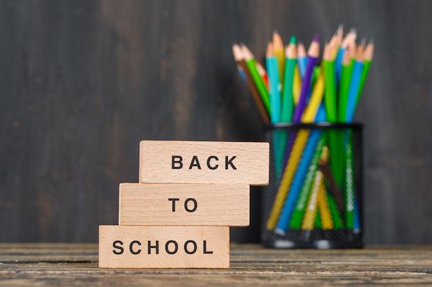 Di nuovo al concetto della scuola con i blocchi di legno, matite in supporto sulla vista laterale della tavola di legno. Foto Gratuite