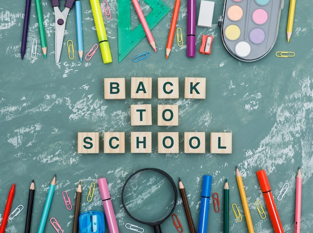 Back to school concept with wooden cubes, magnifying glass, school supplies on plaster background flat lay. Free Photo
