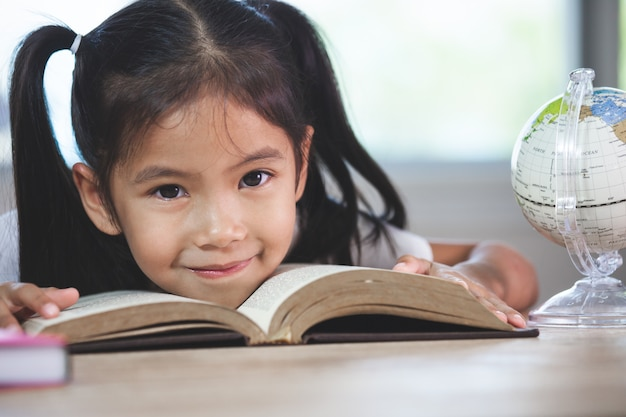 Back to school. cute asian child girl with a book smiling in the classroom Premium Photo