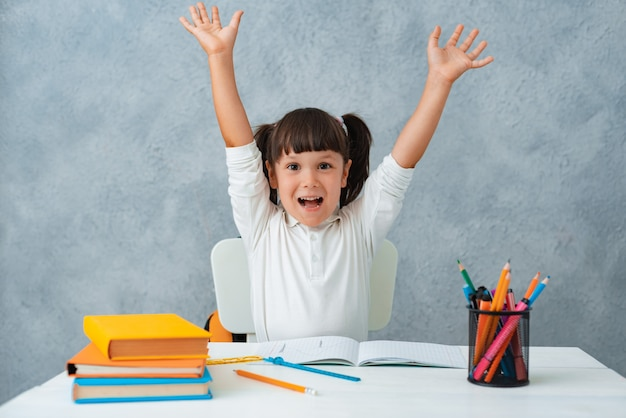 Back to school. cute child schoolgirl sitting at a desk in the room. Free Photo