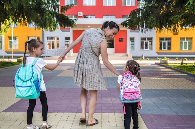 Back to school education concept with girl kids, elementary students, carrying backpacks going to class Free Photo