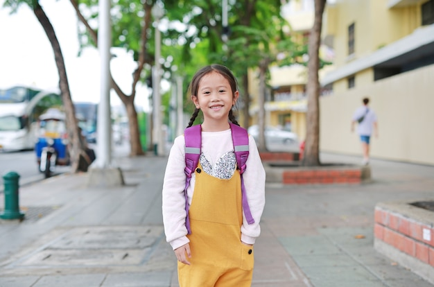 Back to school. happy asian child girl with student shoulder schoolbag. little schoolgirl with a backpack. Premium Photo
