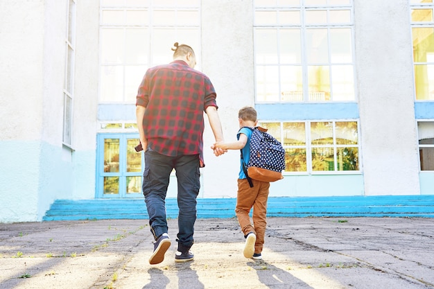 Back to school. happy father and son go to elementary school Premium Photo