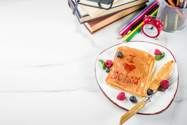 Back to school kids breakfast concept, pancakes with raspberry jam - i love school, on white marble stole, with books, alarm clock, pencils, school supplies. top view Premium Photo