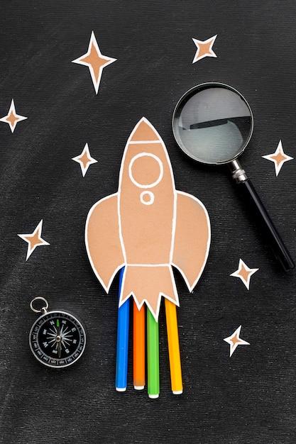 Ritorno a scuola a razzo con lente d'ingrandimento e matite Foto Gratuite