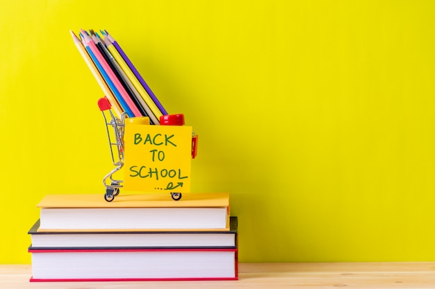 Back to school supplies. books and yellow background on wooden table Premium Photo