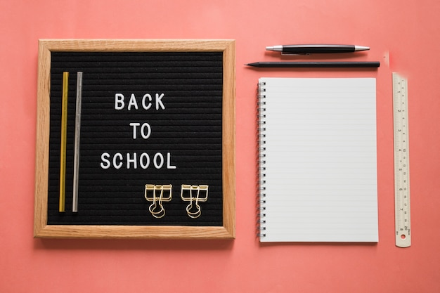 Back to school text on slate with stationeries on colorful background Free Photo