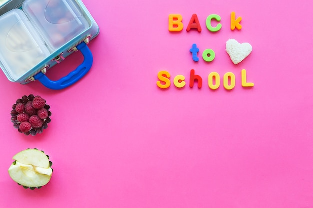 Back to school writing near fruits and lunchbox Free Photo