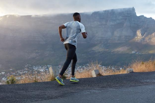 活動中のアクティブな浅黒い肌の男のバックショットは、山道を横切って走り、健康的なライフスタイルを導き、フィットするための持久力とモチベーションを持ち、山を越えてポーズをとり、自然を楽しんでいます 無料写真