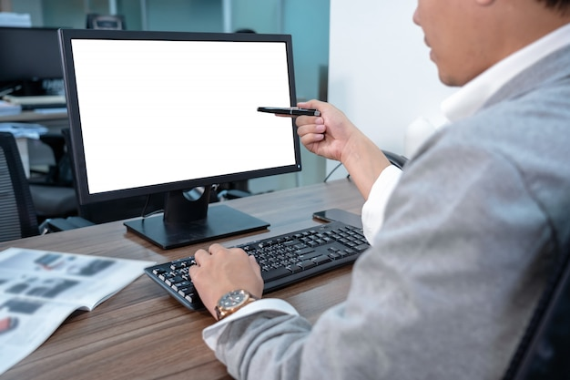 Back side of asian businessman in formal suit using and pointing the pen to computer screen Premium Photo