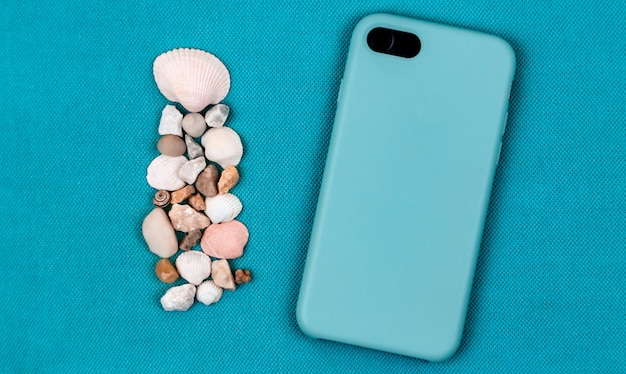 Back side black mobile phone with sea shells Premium Photo