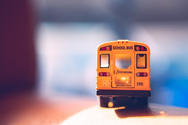 Back side of miniature yellow school bus with sunlight - vintage filter Premium Photo