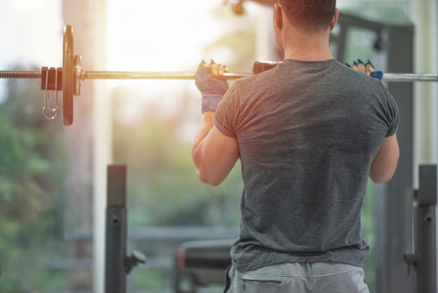 Back side od strong muscular asian man lifting weights exercise his breast in fitness gymnasium,sport and healthy concept. Premium Photo