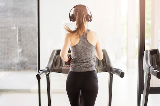 Back sport woman jogging on treadmill in gym, healthy lifestyle Premium Photo