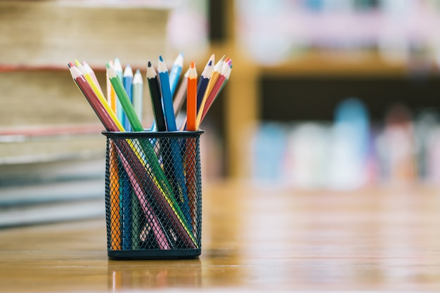 Обратно в школу фон с книгой и деревянными цветными карандашами в корзине Premium Фотографии