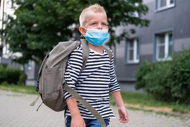 Обратно в школу. мальчик в маске и рюкзаках защиты и безопасности от коронавируса. ребенок идет в школу после окончания пандемии. студенты готовы к новому учебному году Premium Фотографии