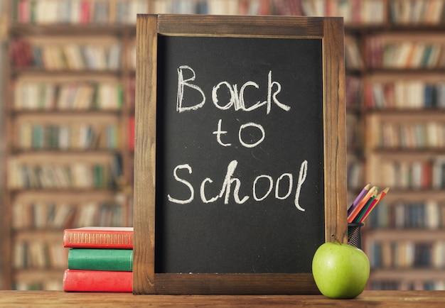 学校に戻る。チョークボード、本、鉛筆 Premium写真