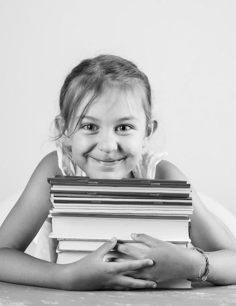 漆喰と白い壁の側面図に学校のコンセプトに戻る。コピーブックや本を抱き締める少女。 無料写真