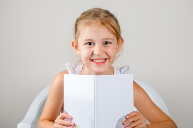 学校のコンセプトに戻る側面図。本を保持している小さな女の子。 無料写真