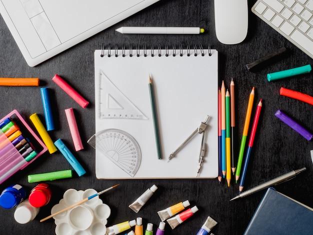図面の本、クレヨン、色鉛筆、ポスターの色、グラフィックタブレット、キーボード、マウスコンピューター、コピースペースを持つ黒い木製の背景に学校の文房具と学校概念に戻る Premium写真