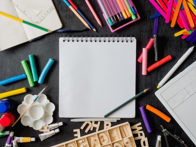 図面の本、クレヨン、色鉛筆、ポスターの色、グラフィックタブレット、キーボード、マウスコンピューター、黒い木製の背景に学校の文房具と学校概念に戻る Premium写真
