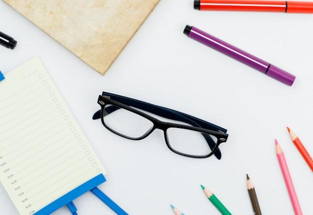 Обратно в школу концепции с очками, школьные принадлежности, ежедневник на белом столе плоской планировки. Бесплатные Фотографии