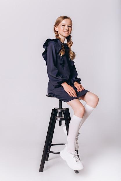 学校に戻る。白い背景の上の制服でかわいい愛らしい白人ブロンディの女の子 Premium写真