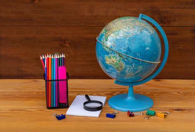Обратно в школу! глобус, модель земли, учебный материал на деревянном столе на глобусе азии и австралии. Premium Фотографии