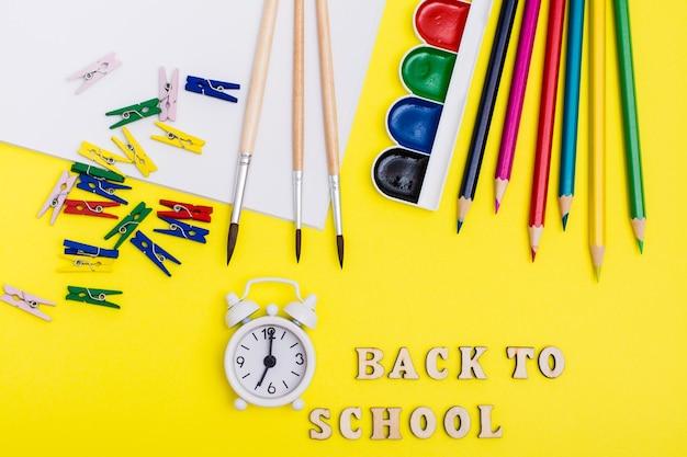 学校に戻る。絵画用品、目覚まし時計、黄色の背景に木製の文字で碑文。上面図 Premium写真