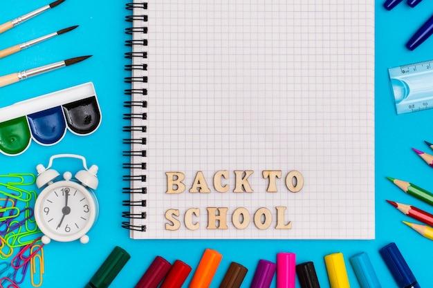 学校に戻る。文房具、目覚まし時計、青色の背景にノートに木製の文字で碑文 Premium写真