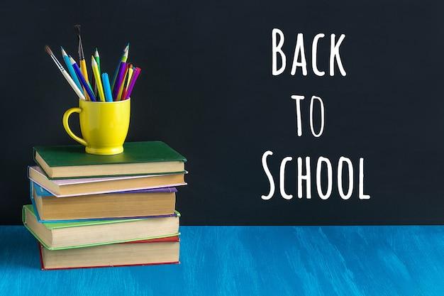 Обратно в школу текст на черной доске и канцелярских принадлежностей в желтой кружке на стопку книг на синем столе. Premium Фотографии